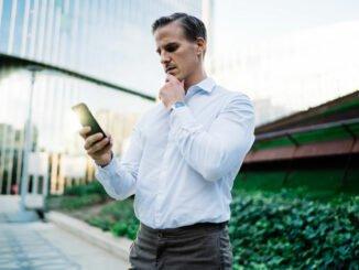 Mann hat iPhone mit leerem Akku in der Hand.