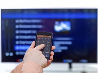 Mann steuert Fernseher mit Smartphone.