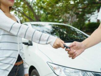 Privater Autoverküfer übergibt Autoschlüssel.
