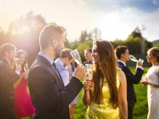 Passend gekleidete Hochzeitsgäste trinken Champagner.