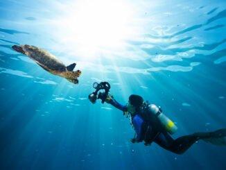 Frau macht Unterwasserfotografie mit Kompaktkamera.
