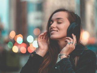 Musikliebhaberin hört verträumt Musik über Kopfhörer.