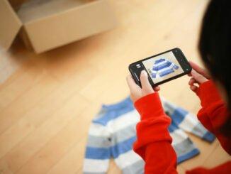 Frau inseriert mit Handy Kleinanzeige im Internet.