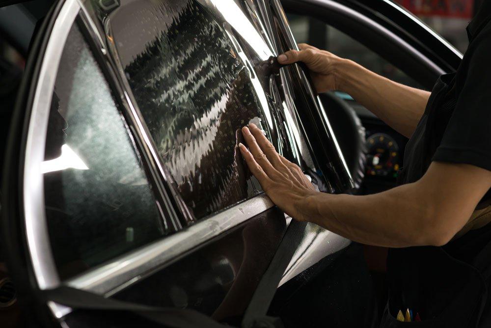 Mann tunt Auto mit dunkler Scheibenfolie.